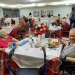 Resident and Staff Holiday Party with people eating.