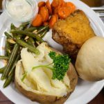Fried chicken with carrots, green beans and a potato on a plate.