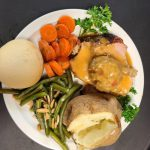 Stuffed porkloin with carrots, green beans and a potato on a plate.