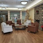 The lobby decorated for Christmas with a Christmas tree, fireplace and chairs.