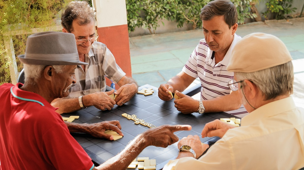Four senior men playing dominoes.