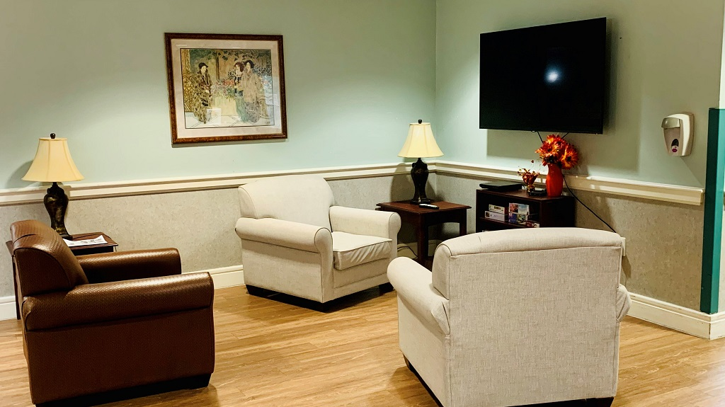 Resident common area in the lobby with chairs and tv.
